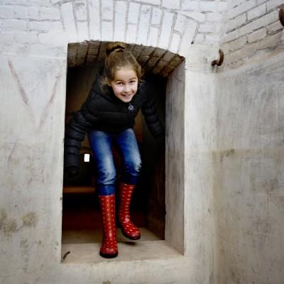 Spelend meisje in de diepe gangen van het Fort Pannerden